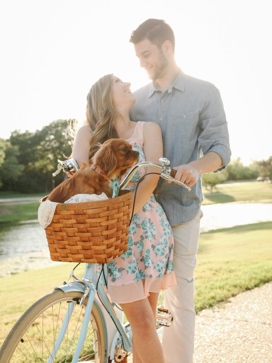 Cole and Caitlin Edwards on a vintage blue bike with a basket during golden hour